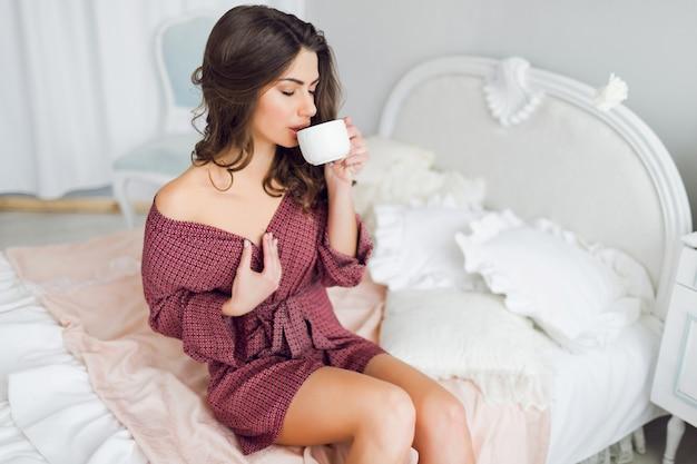 Jovem atraente e sedutora em roupão de banho, sentada em sua cama, bebendo chá ou café, aproveitando a manhã ensolarada preguiçosa