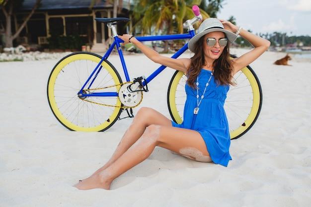 Jovem atraente e sorridente em um vestido azul, sentada na areia em uma praia tropical, com uma bicicleta usando chapéu e óculos escuros