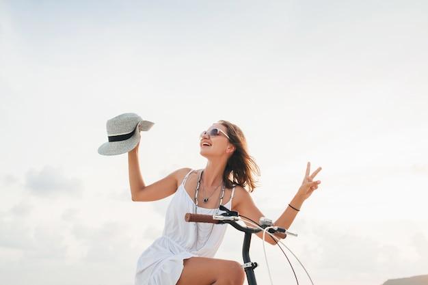 Jovem atraente e sorridente em um vestido branco, andando em uma praia tropical de bicicleta, usando chapéu e óculos escuros