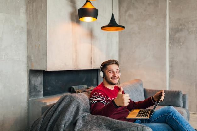 Jovem atraente e sorridente, sentado em casa no inverno, ouvindo fones de ouvido, aluno estudando online, vestindo uma blusa de malha vermelha, segurando no laptop, freelancer, aparecendo o polegar, sinal positivo