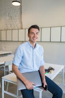 Jovem atraente e sorridente, sentado em um escritório aberto em colaboração, segurando um laptop