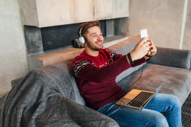 Jovem atraente e sorridente, sentado no sofá em casa no inverno, tirando foto de selfie na câmera do smartphone, vestindo uma blusa de malha vermelha, trabalhando no laptop, freelancer, ouvindo fones de ouvido