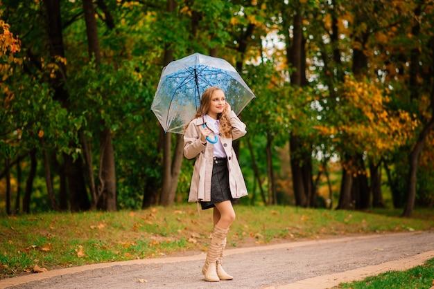 Jovem atraente e sorridente sob o guarda-chuva em uma floresta de outono