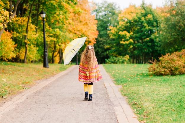 Jovem atraente e sorridente sob o guarda-chuva na floresta de outono