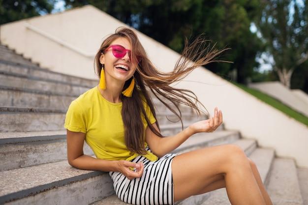 Jovem atraente elegante mulher sorridente se divertindo no parque da cidade, positiva, emocional, cabelo comprido, vestindo blusa amarela, minissaia listrada, óculos de sol rosa, tendência da moda no estilo de verão,