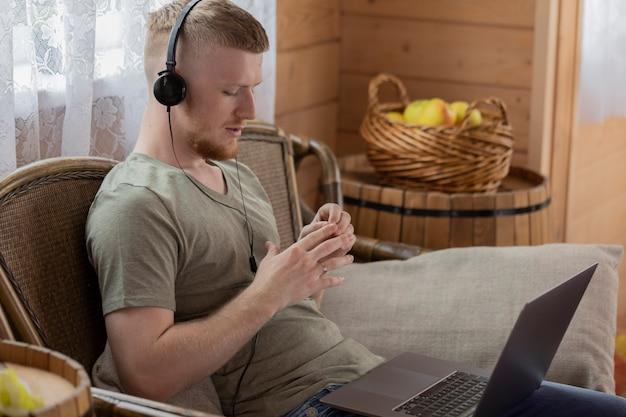 Jovem atraente em fones de ouvido trabalha com laptop, comunica-se em redes sociais, em casa de madeira do campo