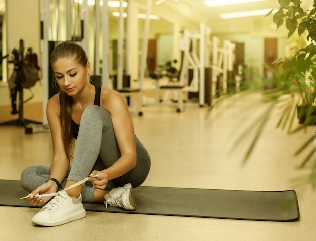 Jovem atraente em forma de mulher amarrando cadarços de tênis esportivos enquanto está sentada em um tapete na academia