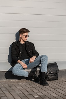 Jovem atraente em óculos de sol da moda com roupas jeans casuais elegantes para jovens e sapatos pretos