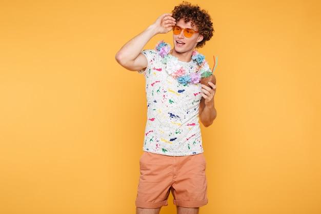 Jovem atraente em óculos de sol segurando coquetel de coco