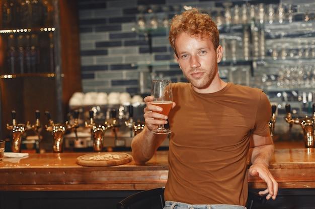 Jovem atraente em pé atrás do bar. homem com uma camiseta marrom tem um copo nas mãos.