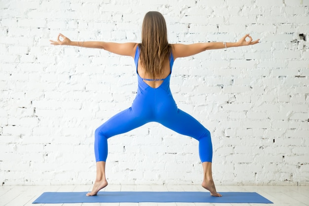Jovem atraente em sumo squat pose, estúdio branco backgrou