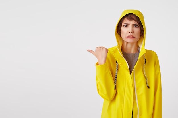 Jovem atraente em uma capa de chuva amarela com uma expressão de nojo no rosto quer chamar sua atenção para o espaço da cópia à esquerda apontando com o dedo, em pé sobre uma parede branca.