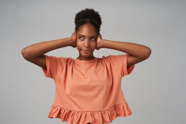 Jovem atraente encaracolada descontente segurando as orelhas com as mãos levantadas enquanto evita sons irritantes, isolada sobre uma parede cinza em uma camiseta rosa