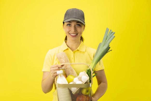 Jovem atraente entregadora de uniforme amarelo e chapéu segurando uma cesta de produtos