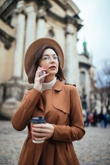Jovem atraente, falando no celular, caminhando ao ar livre em dia frio de outono