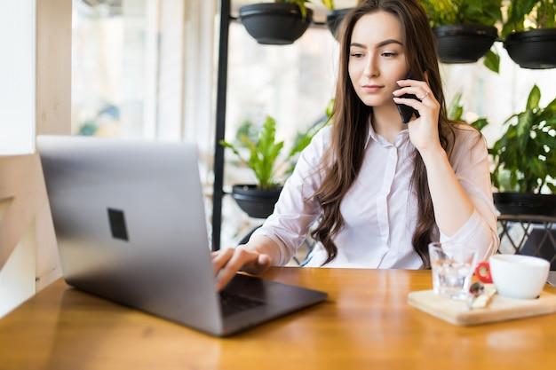 Jovem atraente falando no celular e sorrindo enquanto está sentado sozinho no café durante o tempo livre e trabalhando no computador tablet. mulher feliz descansando no café. estilo de vida