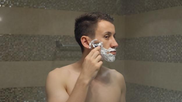 Jovem atraente faz a barba em frente ao espelho pela manhã, antes de um novo dia de trabalho