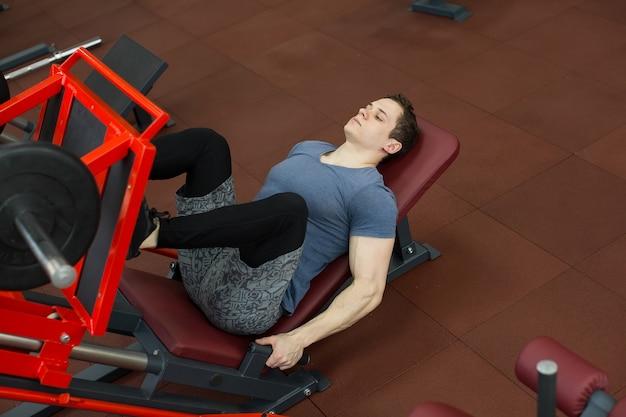 Jovem atraente fazendo leg press na máquina no ginásio