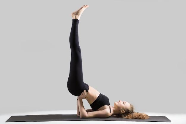 Jovem atraente fazendo viparita karani pose, estúdio cinza b