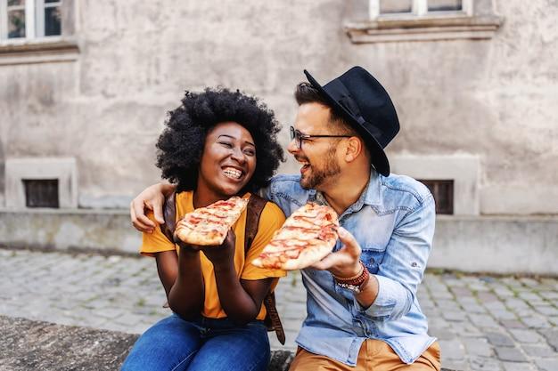 Jovem atraente feliz casal multirracial sentado ao ar livre e comendo pizza.