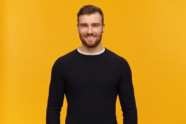 Jovem atraente feliz com barba parece confiante em pé e olhando para a frente sobre a parede amarela