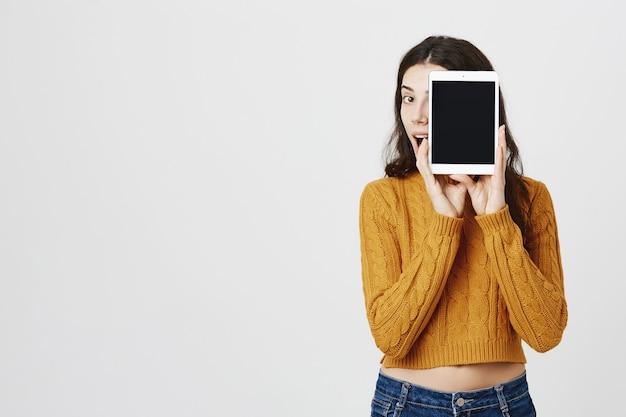 Jovem atraente feliz mostrando a tela do tablet digital Foto gratuita