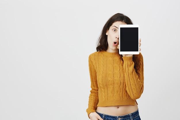 Jovem atraente feliz mostrando a tela do tablet digital