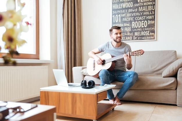 Jovem atraente feliz sentado no sofá tocando violão em casa
