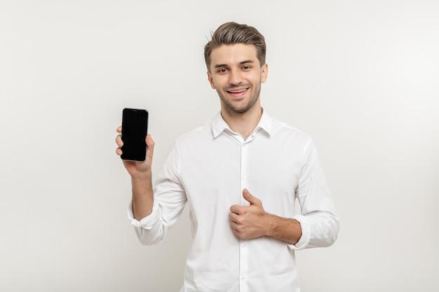 Jovem atraente feliz vestindo uma camisa branca, segurando a tela em branco do smartphone e mostrando o polegar