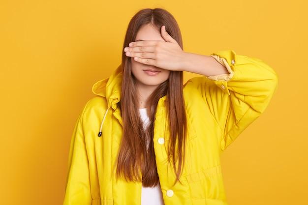 Jovem atraente feminino vestindo jaqueta cobrindo os olhos com as mãos, mulher com cabelos longos, de pé contra a parede amarela, senhora se esconde de sua amiga.