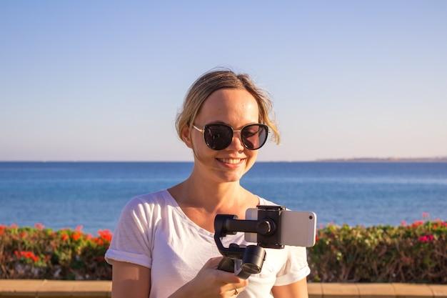 Jovem atraente filma um vídeo de viagens usando o gimbal steadycam e um telefone