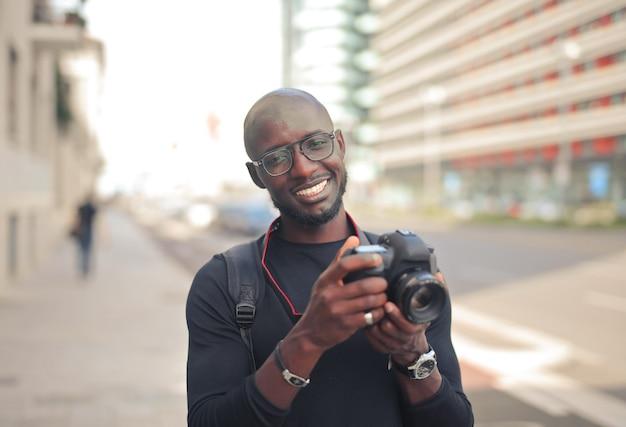 Jovem atraente fotógrafo africano do sexo masculino com uma câmera em uma rua sob o sol