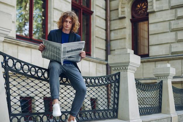 Jovem atraente homem ruivo, cabelos ruivos com cabelos cacheados, lendo um jornal sentado perto de um edifício urbano de estilo antigo. jovens em ação, jovem líder, conhecendo o mundo, as notícias da cidade.
