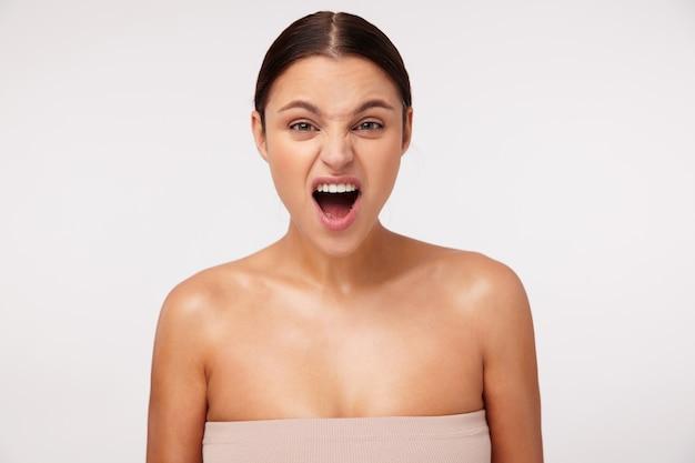 Jovem atraente indignada mulher de cabelos escuros com penteado casual franzindo a testa e mantendo a boca aberta enquanto parece animada, isolada