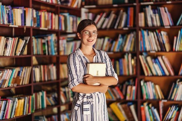 Jovem atraente inteligente sorridente universitária em pé na biblioteca e segurando o livro enquanto olha para a câmera.