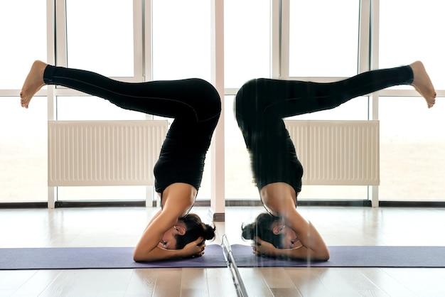Jovem atraente ioga praticando o conceito de ioga, em pé no exercício salamba sirsasana