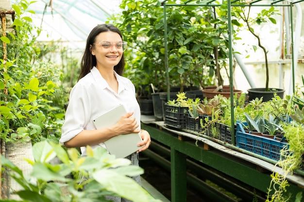 Jovem atraente jardineira de mulheres de negócios de óculos com tablet sorrindo em estufa