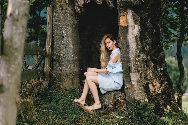 Jovem atraente loira com os pés descalços em um vestido azul sentada na velha árvore
