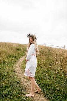 Jovem atraente loira com os pés descalços em um vestido branco com ornamento e coroa de flores na cabeça posando no campo Foto Premium