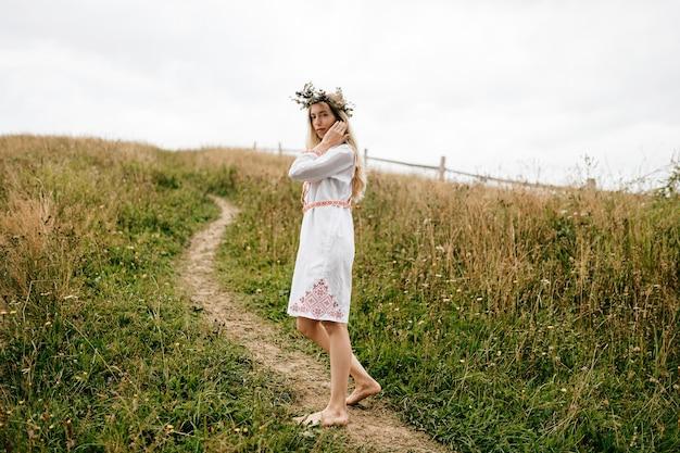 Jovem atraente loira com os pés descalços em um vestido branco com ornamento e coroa de flores na cabeça posando no campo