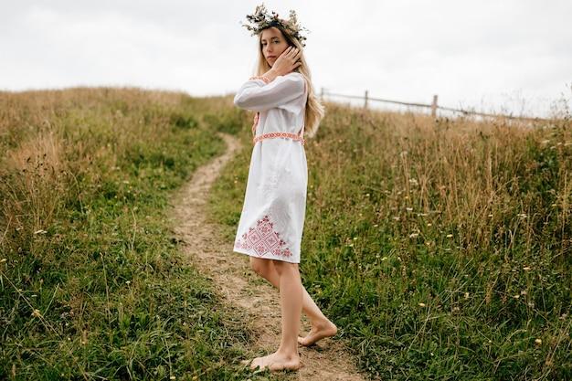 Jovem atraente loira com os pés descalços em um vestido branco com ornamento e guirlanda de flores na cabeça posando no campo