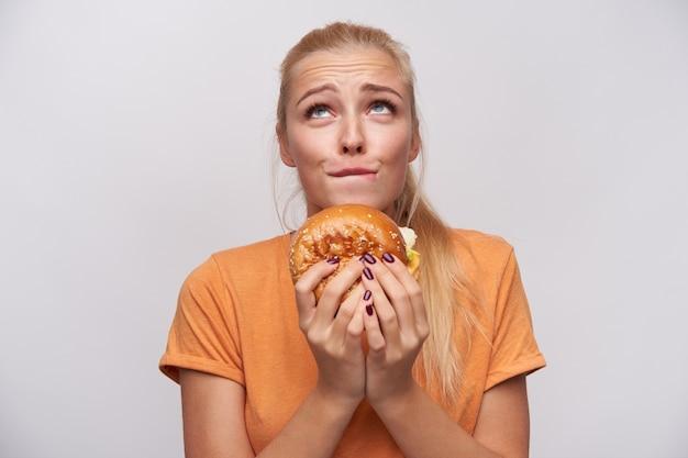 Jovem atraente loira de cabelos compridos com penteado de rabo de cavalo enrugando a testa e mordendo o lábio inferior enquanto olha desculpadamente para cima com junk food nas mãos, isolado sobre o fundo branco