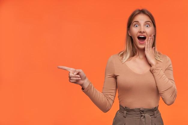 Jovem atraente loira de cabelos curtos espantada com penteado casual, levando a mão ao rosto e olhando surpresa para a frente enquanto aparecia, isolada sobre uma parede laranja