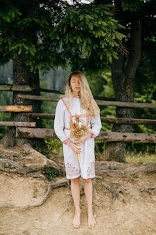 Jovem atraente loira descalça em um vestido branco com ornamento posando com buquê de espigas sobre fundo de cerca de madeira