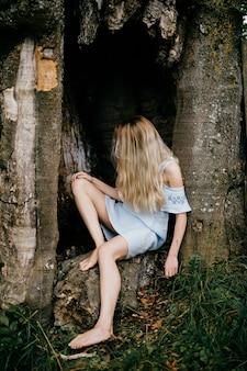 Jovem atraente loira descalça mulher azul vestido romântico sentado na velha árvore