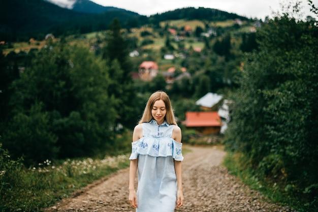 Jovem atraente loira elegante com vestido azul, posando na estrada na zona rural