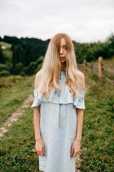 Jovem atraente loira elegante com vestido azul, posando no campo