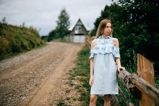 Jovem atraente loira elegante com vestido azul romântico, posando na estrada na zona rural