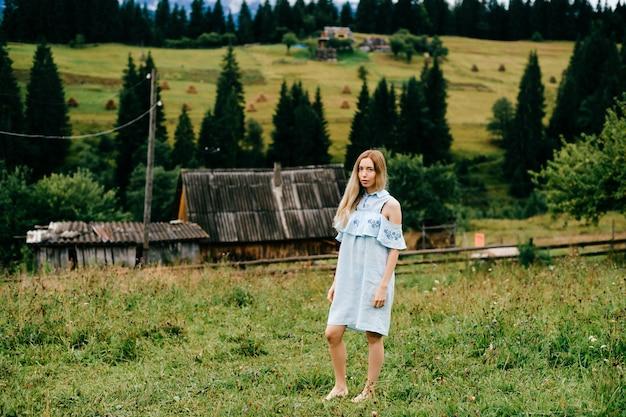 Jovem atraente loira elegante com vestido azul romântico posando no campo em uma casa de campo na zona rural