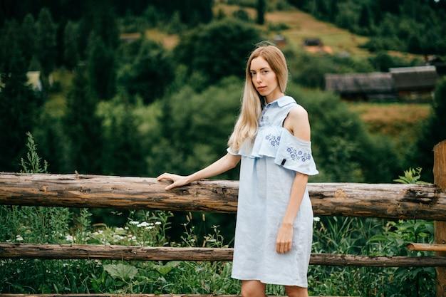 Jovem atraente loira elegante com vestido azul romântico posando no campo